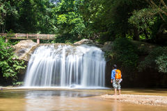 Young man standing in front of waterfall with looking at waterfa Royalty Free Stock Images