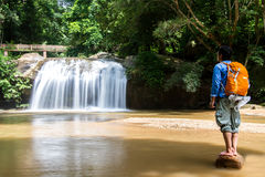 Young man standing in front of waterfall with looking at waterfa Royalty Free Stock Photo