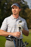 Young man standing by golf bag full of sticks Royalty Free Stock Photography