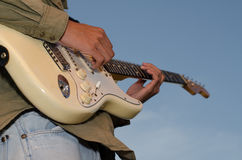 A young man standing guitarist happily under the blue sky in th Royalty Free Stock Photo