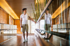 Young Man Standing in Hallway Holding Hand Rail Stock Photography