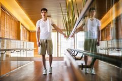 Young Man Standing in Hallway Holding Hand Rail Royalty Free Stock Images