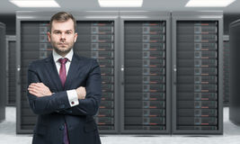 Young man standing with hands crossed in front of server for dat. A storage, processing and analysis, rows of machines at work, front view, blurred background Royalty Free Stock Photo