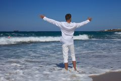 A young man standing hands outstretched at the seashore royalty free stock photo