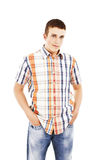 Young man standing with hands in pockets. Isolated on white background Stock Photography