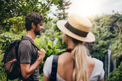 Young man standing with his girlfriend in forest. Outdoor shot of young men standing with his girlfriend in forest. Couple on holiday in nature stock photo