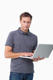 Young man standing with his laptop Stock Photos