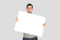 Young man standing and holding a banner Stock Photo