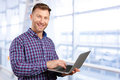 Young man standing, holding laptop computer Royalty Free Stock Photos