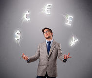 Young man standing and juggling with currency icons Stock Image