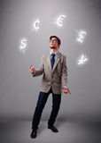 Young man standing and juggling with currency icons Stock Photos