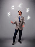 Young man standing and juggling with currency icons Royalty Free Stock Photography
