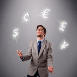Young man standing and juggling with currency icons Stock Photo