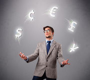 Young man standing and juggling with currency icons Stock Photography