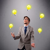 Young man standing and juggling with light bulbs Royalty Free Stock Photography