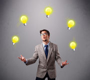 Young man standing and juggling with light bulbs Royalty Free Stock Image