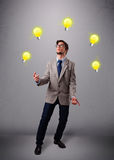 Young man standing and juggling with light bulbs Stock Images