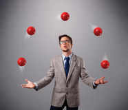 Young man standing and juggling with red balls Stock Photos