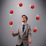 Young man standing and juggling with red balls Royalty Free Stock Photos