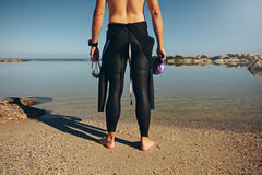 Young man standing on lake wearing wetsuit. Rear view of young man standing on lake wearing wetsuit. Cropped shot of a triathlete preparing for a race wearing a Royalty Free Stock Photography