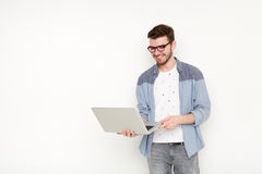 Young man standing with laptop. Handsome guy in glasses holding open notebook in his hand and work on it. Information, technology concept Royalty Free Stock Photography