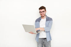 Young man standing with laptop. Handsome guy in glasses holding open notebook in his hand and work on it. Information, technology concept Stock Image