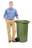 Young man standing by a large green trash can Stock Photo