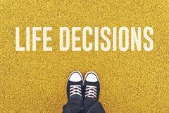 Young man standing at Life Decisions sign. Young man standing on pavement in front of Life Decisions sign printed Royalty Free Stock Photo