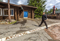 Young man standing on the line of the arctic circle in Rovaniemi Stock Photos