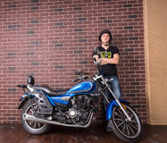 Young Man Standing Beside Motorcycle Against Wall Royalty Free Stock Photos