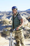 Young Man Standing With Mountain Bike Against Hills Royalty Free Stock Images