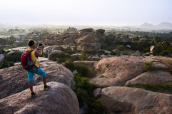 Young man standing on a mountain and making photo of the valley. Young man with backpack standing on a mountain and making photo of the valley Stock Photo