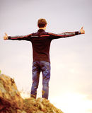 Young Man Standing on Mountain Peak with Arms Raised. Active Lifestyle Concept. Stock Image
