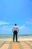Young man standing near the beach Stock Image