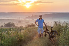 Young man standing near  bicycle in morning sunrise with wonderf. Ul rays and morning mist during calm summer active day Royalty Free Stock Image