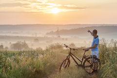 Young man standing near  bicycle in morning sunrise with wonderf Royalty Free Stock Photos