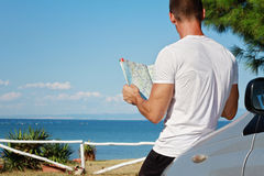 Young man standing near the car and looking at road map. Stock Photo