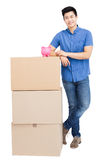 Young man standing near cardboard boxes with piggy bank Royalty Free Stock Image