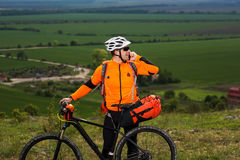Young man standing near the cycle on a green meadow Royalty Free Stock Images