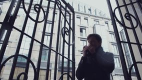 Young man standing near forged gate drinking coffee from plastic cup. Snowfall. Young man in coat standing under canopy of building near forged metal lattice. He stock video footage