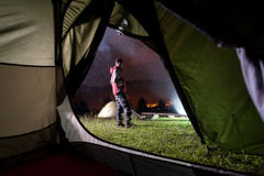 Young man standing near night camping Stock Photos