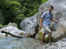 Young man standing near rock in mountain forest. Young man standing near rock in Russian mountain forest Stock Photo