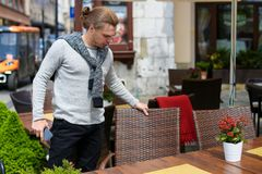 Young man standing near table at street cafe and keeping smartphone. stock photos