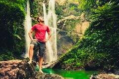 Young man standing near a waterfall in forest. Low angle shot of young man standing near a waterfall in forest and looking away. Male hiker enjoying in the Royalty Free Stock Photo
