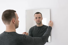 Young man standing near white wall with mirror Royalty Free Stock Photography
