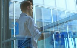 Young man standing near window in his office while thinking about his goals. Young man standing near window in his office while thinking about his goals Stock Image