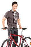 Young man standing next to a bike Stock Image