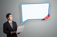 Young man standing next to modern speech bubble copy space and h Royalty Free Stock Photos