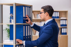 The young man standing next to the shelf with folders Stock Images