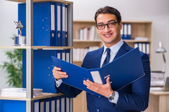 The young man standing next to the shelf with folders Royalty Free Stock Photo